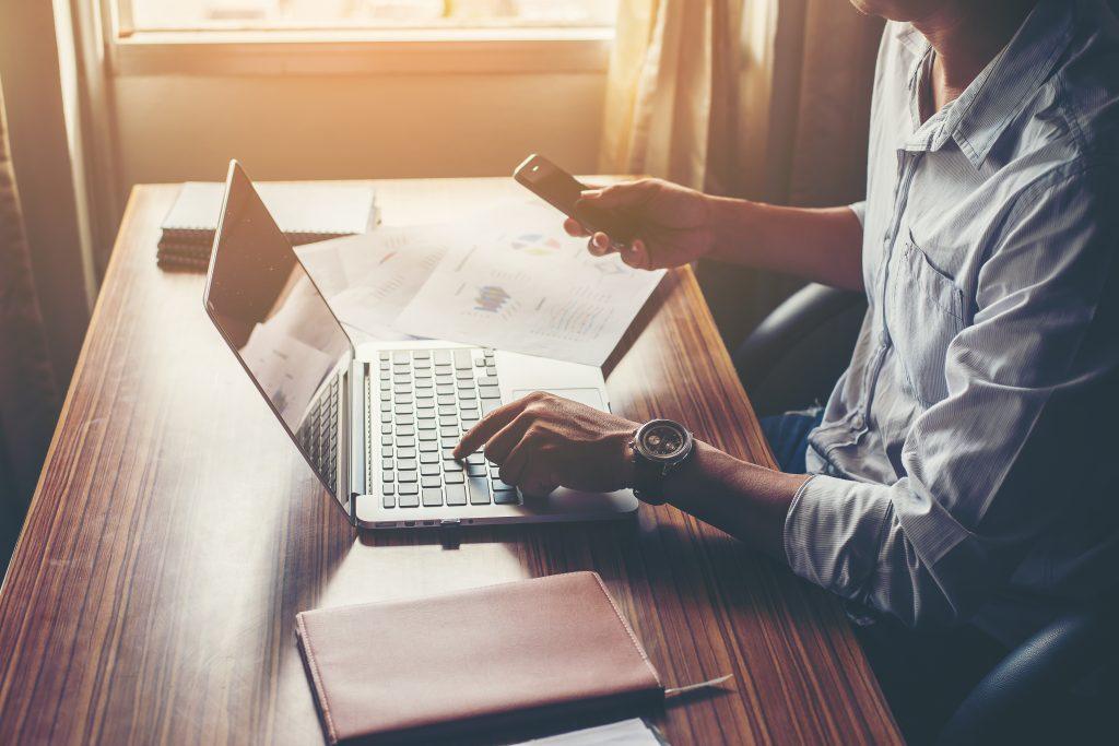 Homem com celular na mão e usando o notebook, simbolizando um ambiente de trabalho em casa.