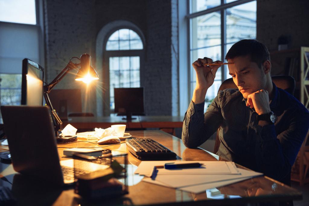 homem trabalhando até tarde, representando horas extras na jornada de trabalho.